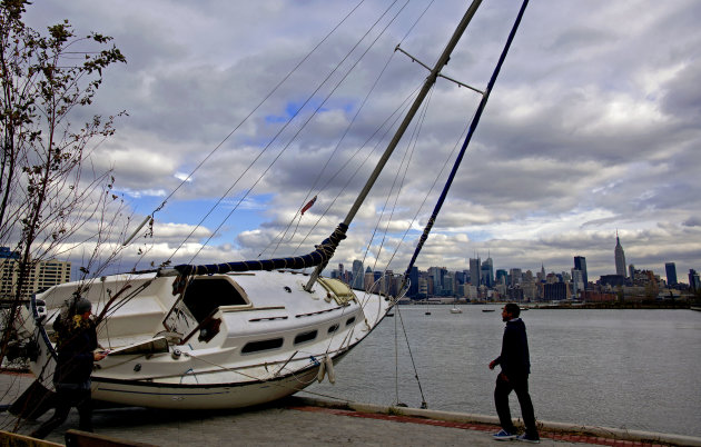 The Manhattan skyline is the backdrop for a sailboat tossed onto the shore in Hoboken, N.J. Wednesday, Oct. 31, 2012 in the wake of superstorm Sandy. Parts of Hoboken are still covered in standing wat