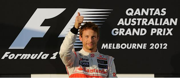 McLaren Mercedes driver and former world champion Jenson Button of Britain gives the 'thumbs-up' signal on the podium after winning the Formula One's Australian Grand Prix in Melbourne on March 18, 20