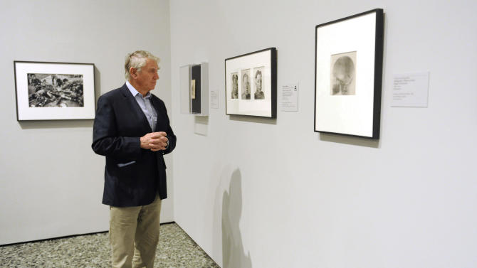In this Thursday, Nov. 8, 2012 photo, photographer Don McCullin views some of the works in the Houston Museum of Fine Arts' war photography exhibit in Houston. The exhibit includes the work of 280 photographers from 28 nations covering the Mexican-American war in 1846 to present-day. McCullin has four photos in the exhibit. (AP Photo/Pat Sullivan)