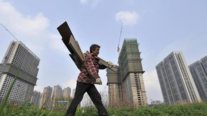 A garbage collector walks past residential and office buildings in construction, in Hefei