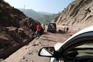 Vehicles make their way along a road after a rockslide in Yiliang. Chinese rescuers are battling blocked roads and downed communications as they continue to search for survivors after the death toll from twin earthquakes rises to 80
