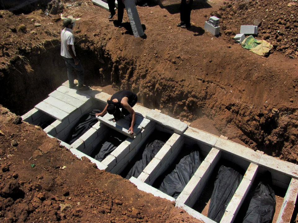 This citizen journalism image provided by Shaam News Network SNN, taken on Thursday, Aug. 9, 2012, purports to show Syrians burying bodies in Daraa, Syria. (AP Photo/Shaam News Network, SNN)THE ASSOCIATED PRESS IS UNABLE TO INDEPENDENTLY VERIFY THE AUTHENTICITY, CONTENT, LOCATION OR DATE OF THIS CITIZEN JOURNALIST IMAGE