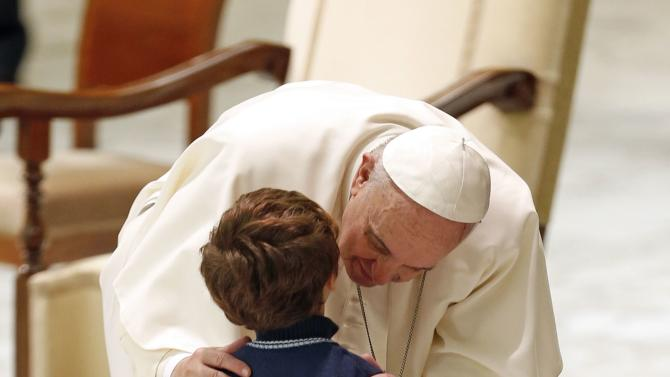 Pope Francis kisses a child during a meeting with large families in Paul VI hall at the Vatican