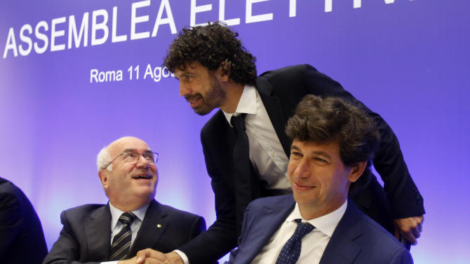 Italian Soccer Federation (FIGC) candidate presidents Carlo Tavecchio, left, and Demetrio Albertini greet Soccer Players Association (AIC) President Damiano Tommasi, center, prior to the start of the national elective assembly in Fiumicino, near Rome, Monday, Aug. 11, 2014. (AP Photo/Riccardo De Luca)