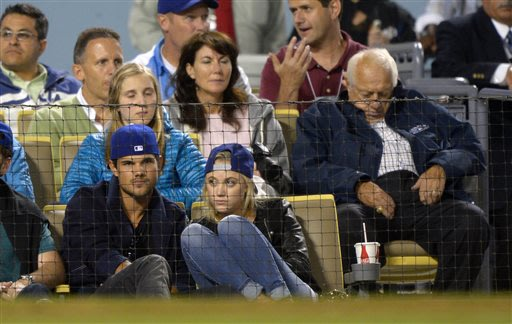 Actor Taylor Lautner, left, and Sara Hicks, center, watch the Los Angeles Dodgers play the St. Louis Cardinals during a baseball game as former Dodgers manager Tommy Lasorda, right, appears to sleep,