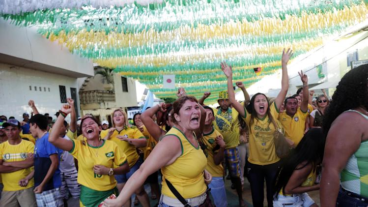 Fans celebrate a goal by Brazil as it plays   Cameroon during the 2014 soccer World Cup in Manaus, Brazil, Monday, June 23, 2014