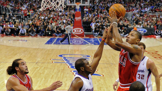 Chicago Bulls guard Derrick Rose, right, puts up a shot as Los Angeles Clippers guard Chris Paul, center, defends and Bulls center Joakim Noah, left, looks on during the first half of their NBA basketball game, Friday, Dec. 30, 2011, in Los Angeles. (AP Photo/Mark J. Terrill)