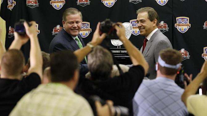 Photographers take pictures of Alabama head coach Nick Saban and Notre Dame head coach Brian Kelly posing with The Coaches' Trophy during a news conference for the BCS National Championship college football game Sunday, Jan. 6, 2013, in Miami.  (AP Photo/Chris O'Meara)