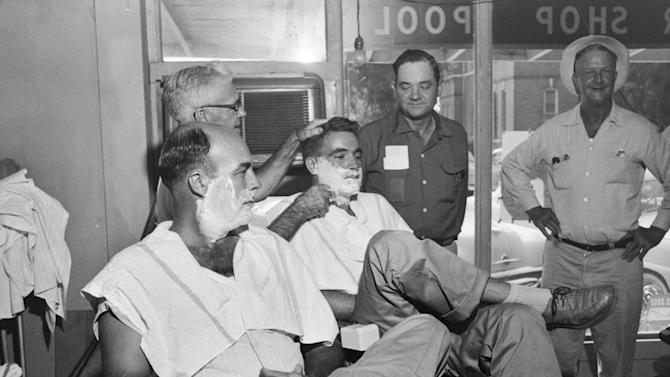 FILE - In this Sept. 6, 1955 file photo, John W. Milam, 36, left, watches as a barber lathers the face of Roy Bryant, 24, center, in Sumner, Miss. The shave came just before the half-brothers were arraigned on charges they kidnapped and murdered Emmett Louis Till, a 14-year-old black boy visiting from Chicago. At right is Sheriff's Deputy G. Melton. (AP Photo/Gene Herrick)