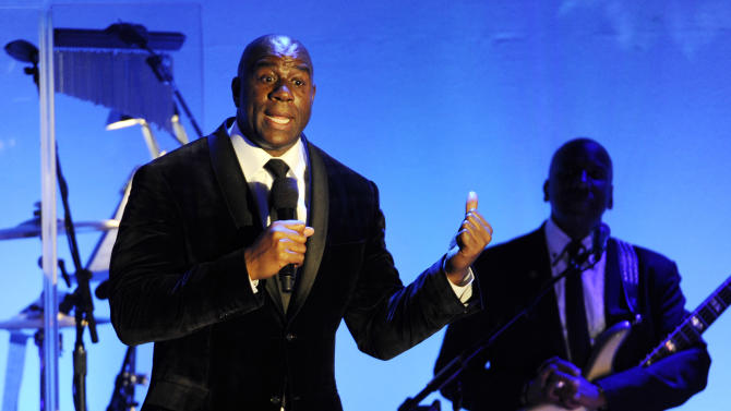 """FILE - In this Oct. 11, 2014, file photo, Earvin """"Magic"""" Johnson addresses the audience after receiving the Brass Ring Award for his humanitarian efforts at the 2014 Carousel of Hope Ball at the Beverly Hilton Hotel in Beverly Hills, Calif. The retired Los Angeles Laker became famous for dishing out assists to his teammates during his Hall of Fame basketball career. Now, as an entrepreneur focused on minority markets, he says he is ready to help Silicon Valley hire more blacks and Latinos to diversify the technology industry's largely white and Asian workforce. (Photo by Chris Pizzello/Invision/AP, File)"""