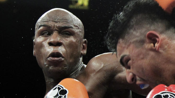 FILE - This Sept. 17, 2011 file photo shows Floyd Mayweather Jr., left, punching Victor Ortiz during their WBC welterweight title fight in Las Vegas. Lawyers for Mayweather say the undefeated champion boxer may never fight again if he's not released from the Las Vegas jail he entered earlier this month. (AP Photo/Julie Jacobson, File)