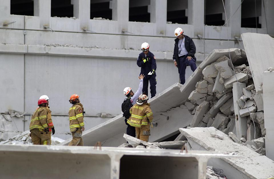 Firefighters look over the rubble after a section of a parking garage under construction at a Miami-Dade College campus collapsed, Wednesday, Oct. 10, 2012 in Doral, Fla., killing one worker and trapping at least two others in the rubble, officials said. (AP Photo/J Pat Carter)