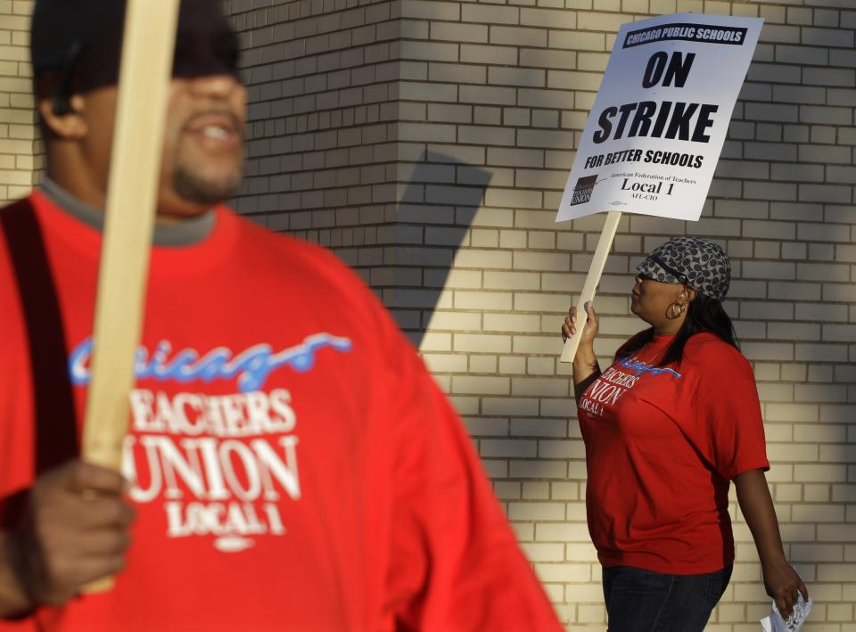 Chicago teachers Michael Williams and Alma Hill walk a picket line outside Benjamin Banneker Elementary School in Chicago, early Monday, Sept. 10, 2012, after the teachers went on strike for the first time in 25 years. Union and district officials failed to reach a contract agreement despite intense weekend negotiations. (AP Photo/M. Spencer Green)