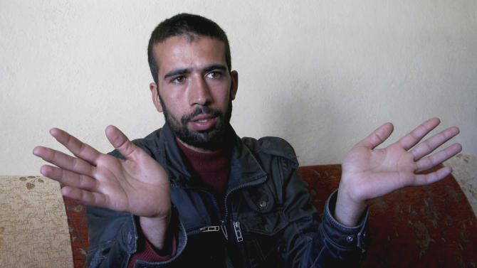 Ahmad Mihbzt, a low-ranking Syrian rebel commander, gestures during an interview with The Associated Press in the village of Gorentas in Hatay province, Turkey, Sunday, March 18, 2012. Mihbzt says he recently fled to Turkey with his men when his unit ran out of ammunition in a clash against Syrian government troops. His story reveals a bleak future for the Free Syrian Army which is still hoping to oust President Bashar Assad's powerful and loyal forces but facing a shortage of weapons, ammunition and money. (AP Photo/Selcan Hacaoglu)