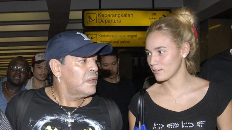 Diego Maradona and his girlfriend Rocio Olivia arrive at the airport in Jakarta on June 29, 2013 for a visit to Indonesia