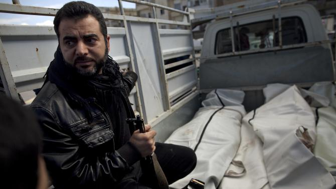A man sits next to the bodies of a three Free Syrian Army fighters allegedly killed by the Syrian Army during their funeral in Idlib, north Syria, Saturday, March 3, 2012. (AP Photo/Rodrigo Abd)