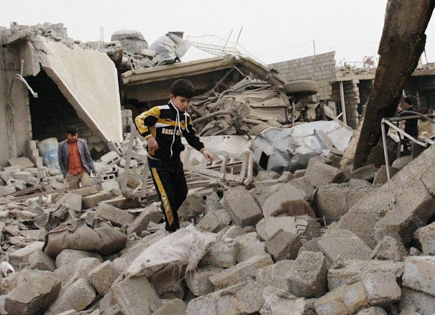 A boy walks in rubble at the scene of a car bomb attack in al-Mouafaqiyah, a village inhabited by families from the Shabak ethnic group, near the city of Mosul, 225 miles (360 kilometers) northwest of Baghdad, Iraq, Monday, Dec. 17, 2012. Three car bomb explosions in Iraqs north on Monday, killing and wounding scores of people, police said. (AP Photo)