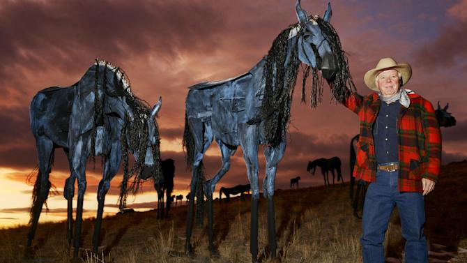 In this photo taken on Monday, Dec. 16, 2103, sculptor Jim Dolan, from Belgrade, Mont., poses for a photo with his steel horse herd sculptures that are on display on a hillside near Three Forks, Mont. Dolan, who spent about 15 months making them, recently discovered that three of his sculptures have been stolen. (AP Photo/Bozeman Daily Chronicle, Mike Greener)