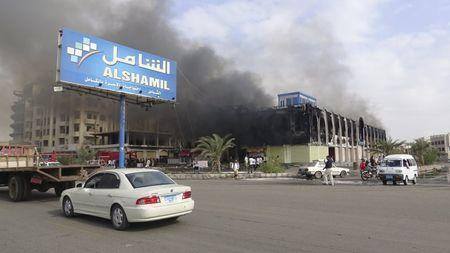 Smoke rises from a mall after clashes in Yemen's southern port city of Aden