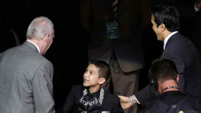 Sebastien De la Cruz is greeted by San Antonio Spurs' Gregg Popovich, left, and Miami Heat's Erik Spoelstra after singing the national anthem before Game 4 of the NBA Finals basketball series, Thursday, June 13, 2013, in San Antonio. (AP Photo/David J. Phillip)