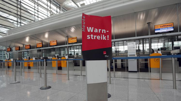 Empty counters and a poster that reads ' Warning Strike' is seen during a warning strike of employees of the German airliner Lufthansa at the airport in Munich, southern Germany, Monday, April 22, 2013. (AP Photo/Matthias Schrader)