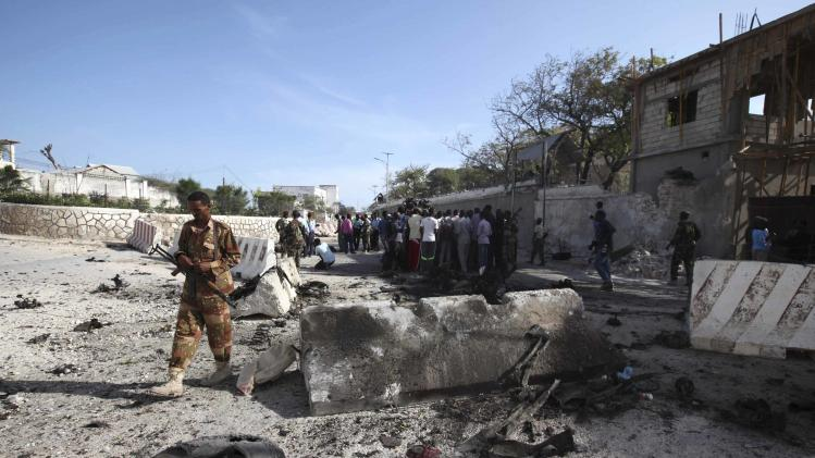 A Somali government soldier secures the scene of a suicide attack next to the gate of the Presidential Palace in Mogadishu