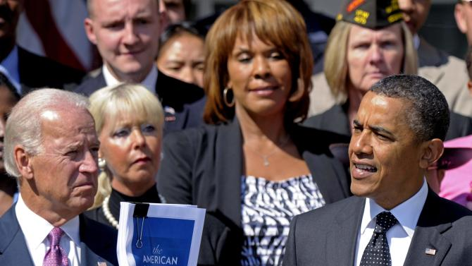 President Barack Obama, accompanied by Vice President Joe Biden, and others, holds up a copy of his American Jobs Act during a statement in the Rose Garden of the White House in Washington, Monday, Sept. 12, 2011. (AP Photo/Susan Walsh)