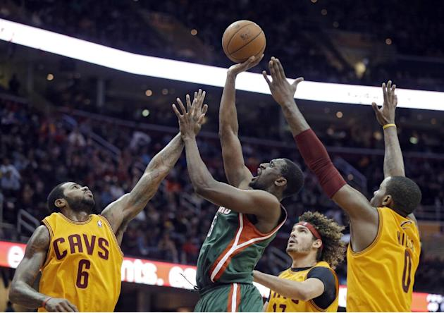 Milwaukee Bucks' Ekpe Udoh shoots against Cleveland Cavaliers' Earl Clark (6), Anderson Varejao and C.J. Miles, right, in the fourth quarter of an NBA basketball game Friday, Dec. 20, 2013, in