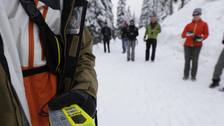In this Jan. 4, 2013 photo, Students using avalanche scanners look for a target during an avalanche safety course held on Snoqualmie Pass in Washington state. Where backcountry safety education once stressed the mechanics of avalanches and snow science, training courses now incorporate a focus on human factors such as how to make better decisions, manage group dynamics and speak up should danger arise. (AP Photo/Ted S. Warren)