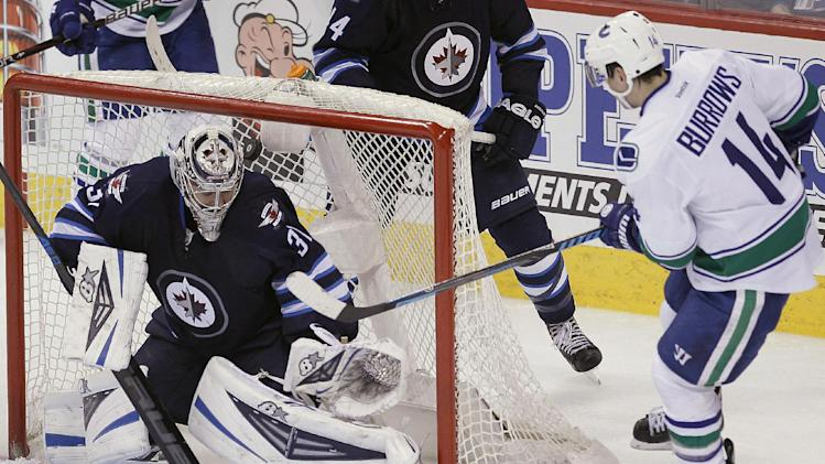 Vancouver Canucks' Alexandre Burrows (14) knocks the puck out of the air and in behind Winnipeg Jets goaltender Ondrej Pavelec (31) to tie the game 2-2 during the third period of an NHL hockey game Wednesday, March 12, 2014, in Winnipeg, Manitoba. The Canucks won 3-2 in a shootout