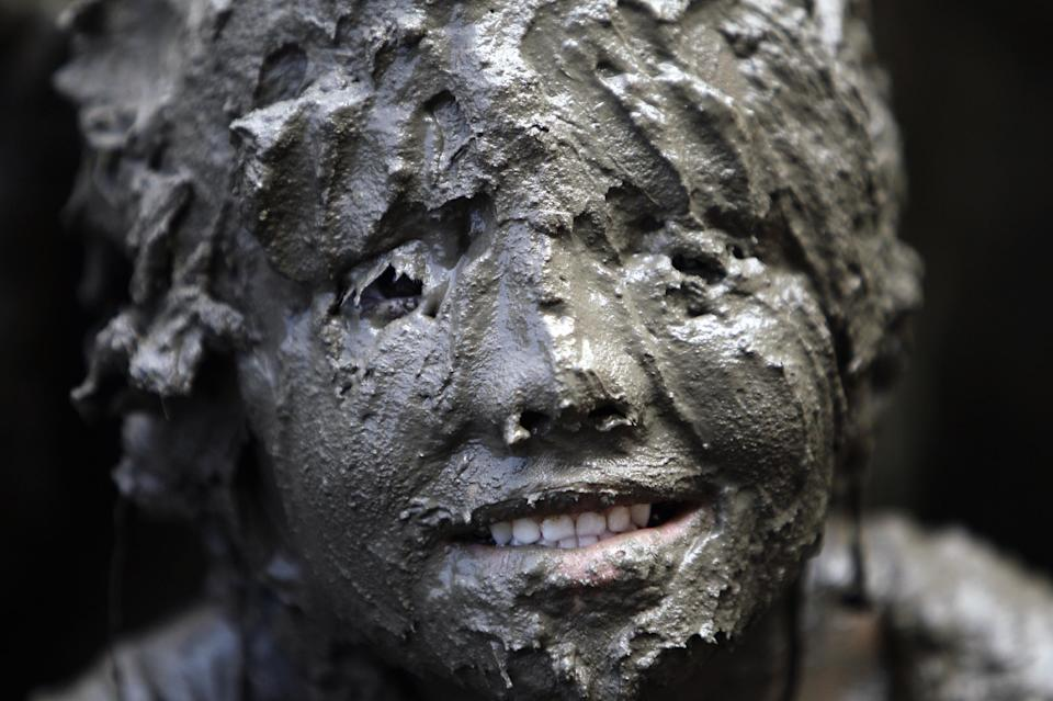 Lilli Alcala, 7, of Redford, smiles while covered in mud in Westland, Mich., Tuesday, July 9, 2013. Hundreds of kids enjoyed the annual Mud Day event in a 7-by-150-foot mud pit. (AP Photo/Paul Sancya)