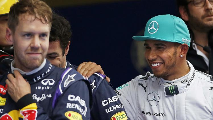 Mercedes Formula One driver Hamilton celebrates with second-fastest Red Bull Formula One driver Ricciardo and third-fastest Vettel of Germany, after taking pole position at qualifying session of Chinese F1 Grand Prix