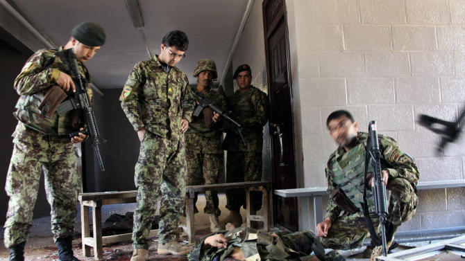 Afghan army soldiers stand around a killed Taliban, dressed as an Afghan army soldier, in the destroyed courthouse in Farah, western Afghanistan, Thursday, April 4, 2013. Suicide bombers disguised as Afghan soldiers stormed a courthouse Wednesday in a failed bid to free more than a dozen Taliban prisoners in western Afghanistan, officials said. Tens of people, including the nine attackers were reported killed in the fighting. The assault in Farah province was the latest example of the Taliban's ability to strike official institutions despite tight security measures. (AP Photo/Hoshang Hashimi)