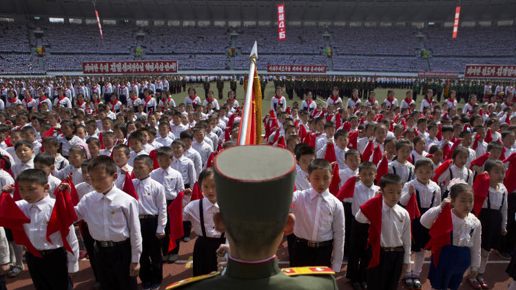 North Korean children hold up red scarves to be tied around their necks during an induction ceremony into the Korean Children's Union, the first political organization for North Koreans, held at a stadium in Pyongyang on Friday, April 12, 2013. (AP Photo/David Guttenfelder)