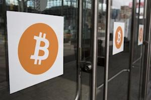Bitcoin themed stickers stand attached to glass doors during the Inside Bitcoins: The Future of Virtual Currency Conference in New York