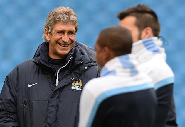 Manchester City's manager Manuel Pellegrini (L) supervises a training session at The City of Manchester stadium, on November 26, 2013, on the eve of their UEFA Champions League Group D match again