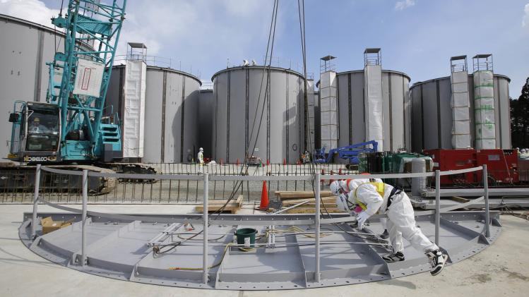 Men work in front of welding storage tanks for radioactive water, under construction in the J1 area at Fukushima Daiichi nuclear power plant in Fukushima