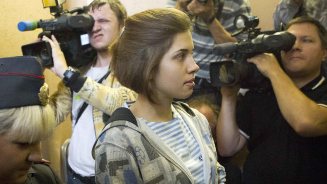 "Nadezhda Tolokonnikova, center, a member of feminist punk group Pussy Riot is escorted to a court room in Moscow, Russia, Friday, July 20, 2012. The trial of feminist punk rockers who chanted a ""punk prayer"" against President Vladimir Putin from a pulpit inside Russia's largest cathedral started in Moscow on Friday amid controversy over the prank that divided devout believers, Kremlin critics and ordinary Russians. (AP Photo/Misha Japaridze)"