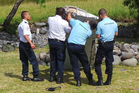French gendarmes and police inspect a large piece of plane debris which was found on the beach in Saint-Andre, on the French Indian Ocean island of La Reunion