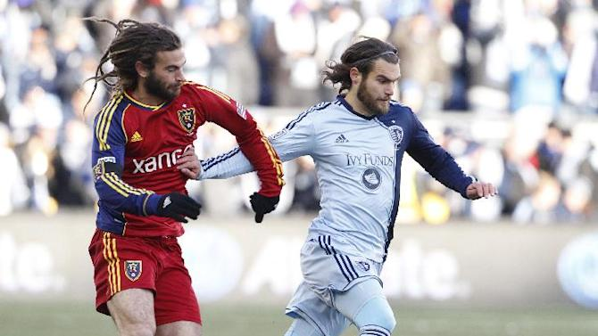 Real Salt Lake midfielder Kyle Beckerman, left, and Sporting Kansas City forward Graham Zusi, right, battle for the ball during the first half of the MLS Cup final soccer match in Kansas City, Kan., Saturday, Dec. 7, 2013. (AP Photo/Colin E. Braley)