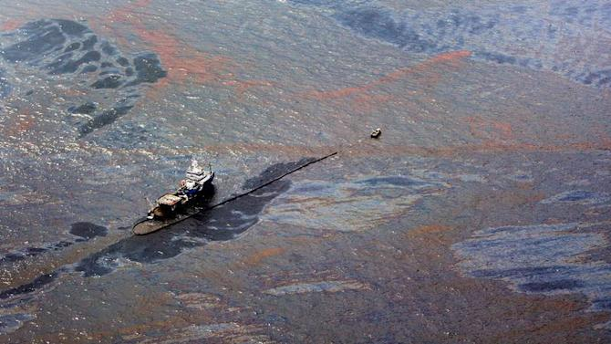 Oil floats on the surface of the Gulf of Mexico around a work boat at the site of the Deepwater Horizon oil spill in the Gulf of Mexico