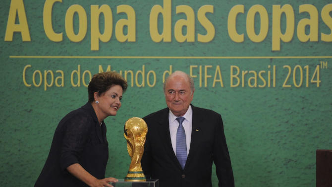 Brazilian President Dilma Rousseff and FIFA President Joseph Blatter stand next to the World Cup trophy during its presentation in Brasilia on June 2, 2014