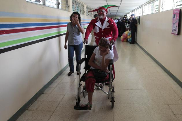 A clown pushes the wheelchair of a cancer patient at the La Mascota children's hospital in Managua