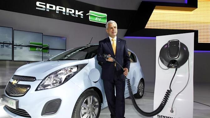 Sergio Rocha, president and CEO of GM Korea poses next to Spark EV at the Seoul motor show in Goyang