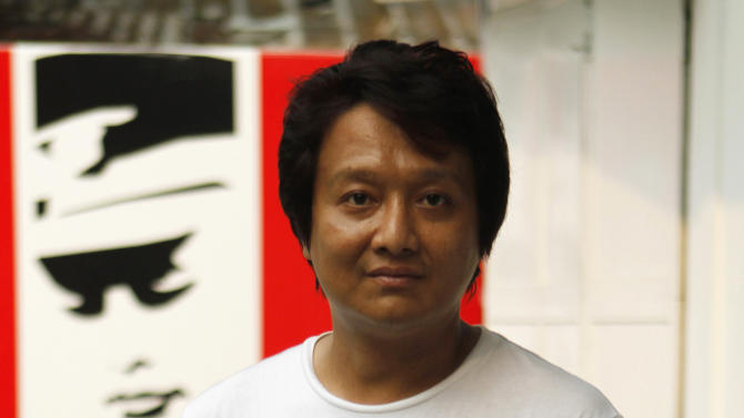 """In this photo taken April 3, 2012, Myanmar filmmaker Htun Zaw Win poses outside his office in Yangon, Myanmar. When Htun Zaw Win decided to make a short comedy about the tragically bizarre process of getting movies made in his oppressed homeland, he knew exactly what to base it on: Real life.  """"Ban That Scene!"""" makes a daring mockery of this country's dreaded film censorship board, whose members are cast as comical guardians of a tyrannical state's idealized image of itself.  (AP Photo)"""