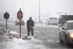 Neal Abernathy clears snow at the entrance of the store…