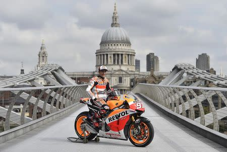 Honda MotoGP rider Marc Marquez of Spain poses on the Millennium Bridge with St Paul's Cathedral seen behind, in London