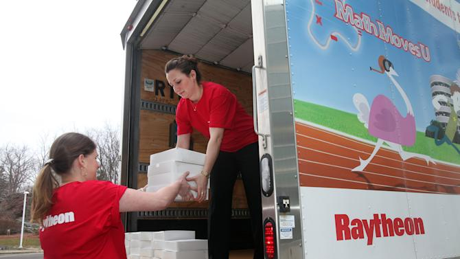 Raytheon Company employees load a truck with fresh apple pies in honor of Pi Day (March 14, or 3.14) at company headquarters in Waltham, Massachusetts.  The pies will be given to math and science teachers at schools located within a 3.14-mile radius to celebrate Pi Day as part of the company's MathMovesU® initiative that encourages kids to pursue careers in the science, technology, engineering and math fields.  (Aynsley Floyd/AP Images for Raytheon Company)