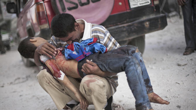 FILE - In this Wednesday, Oct. 3, 2012 photo, a Syrian man cries while holding the body of his son killed by the Syrian Army near Dar El Shifa hospital in Aleppo, Syria. (AP Photo/ Manu Brabo)