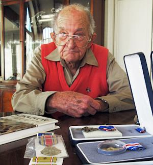 In this Nov. 10, 2011 photo, Tom Harrison, 93, displays his World War II medals at his home in Salt Lake City. Harrison spent several years in a Japanese prisoner of war camp after enduring the brutal Bataan Death March. He returned home to his family, and more than six decades later, just received six medals honoring his service, including the Distinguished Service Cross and the Silver Star. (AP Photo/Brian Skoloff)